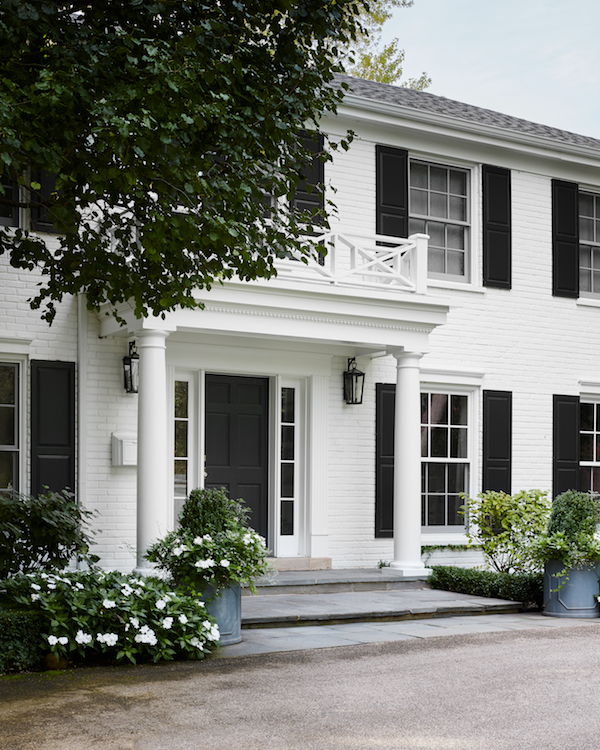 White brick house exterior painted in Custom Mix of Benjamin Moore Linen White and Benjamin Moore White Dove