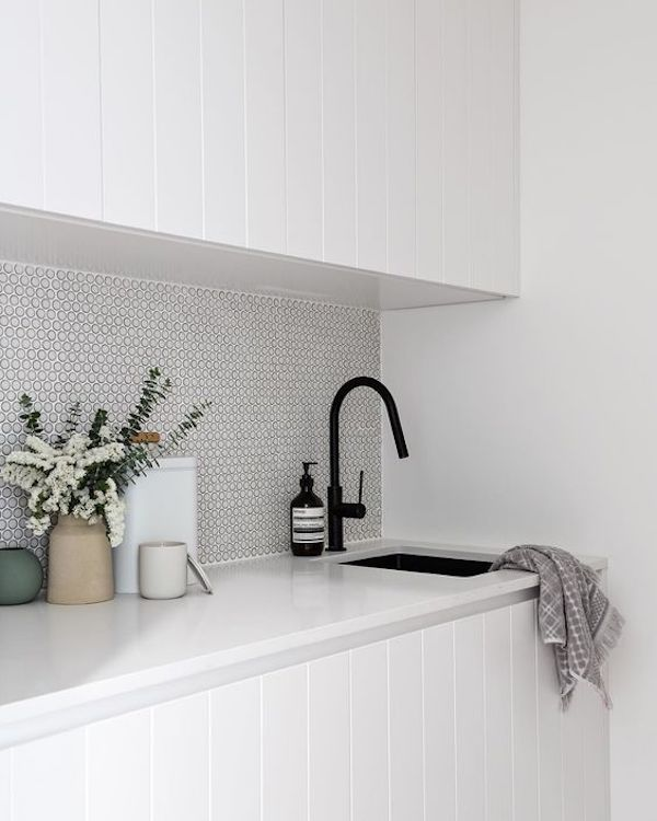 white penny tiles on laudry room backsplash
