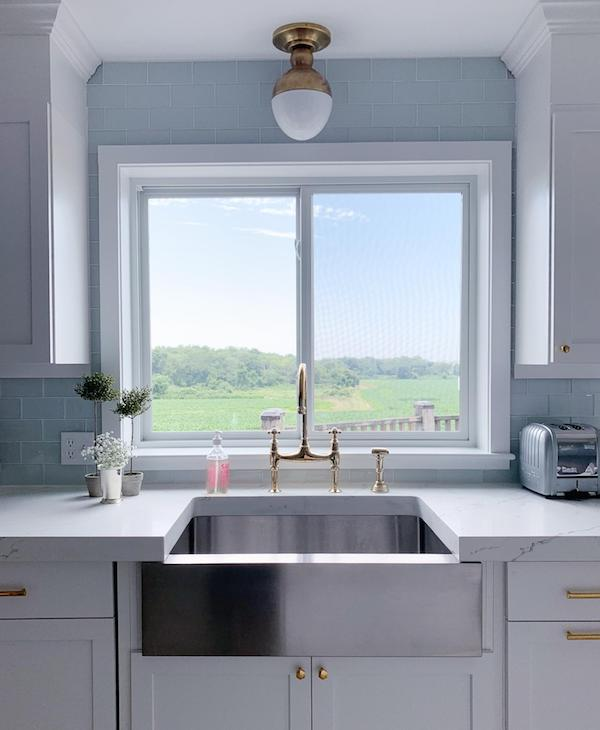 white mitered quartz counter with apron front stainless steel sink