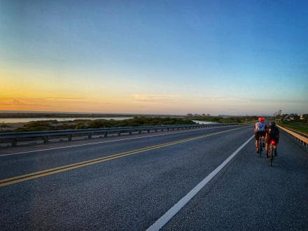 cyclist riding on road as sun sets