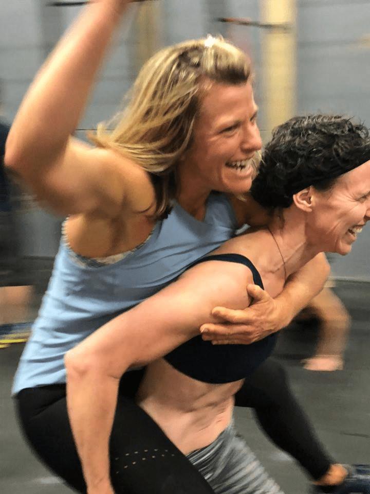 Two women joking while doing a piggyback ride