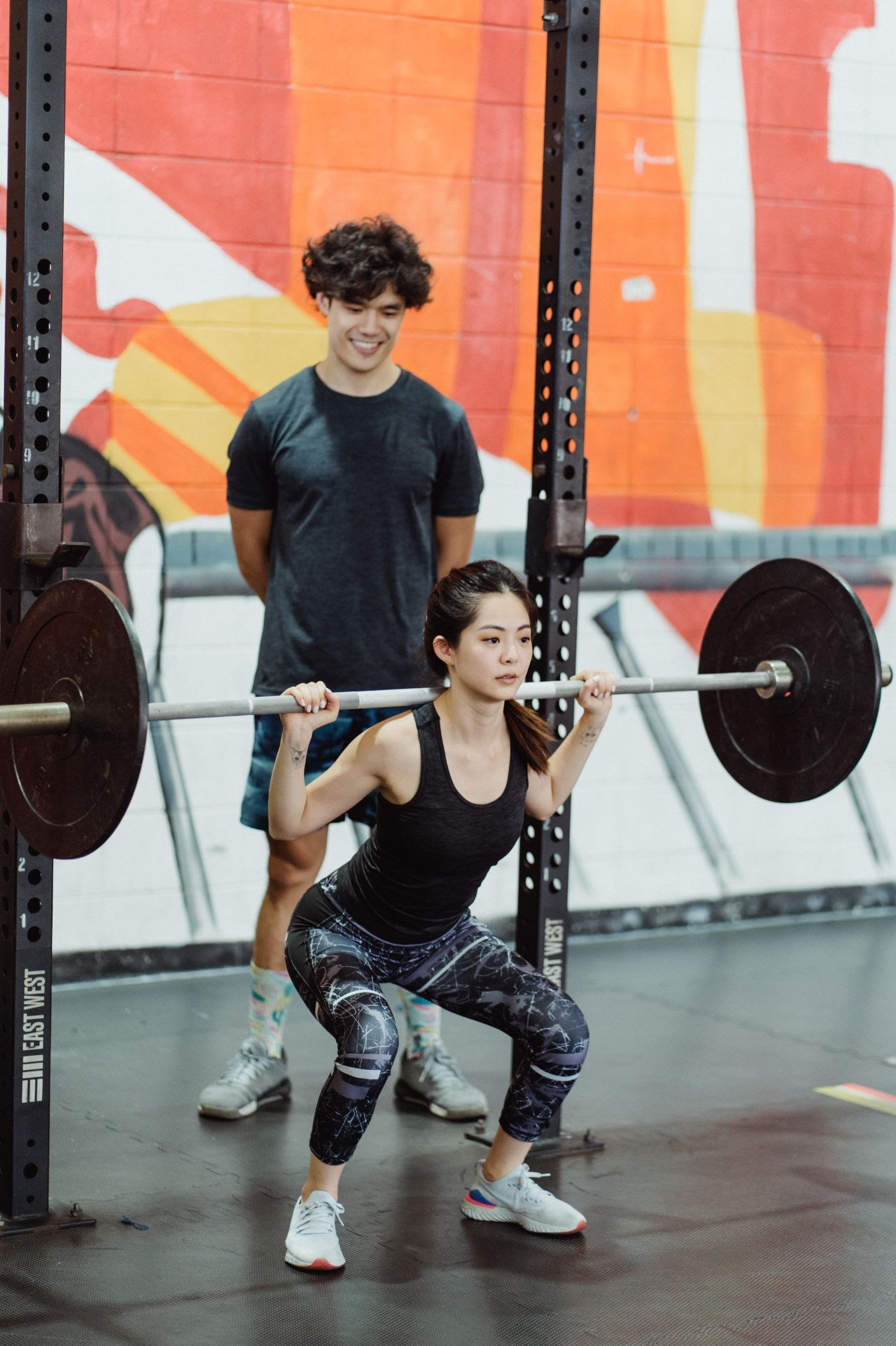 female cyclist improves strength by squatting a heavy weight