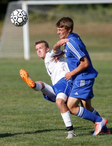 Woodbury, CT- 21 September 2015-092115CM04- Nonnewaug's Nathan Firlings, left, sends the ball up field against Lewis Mills' Kyle Baron during their Berkshire League soccer matchup in Woodbury on Monday. Christopher Massa Republican-American