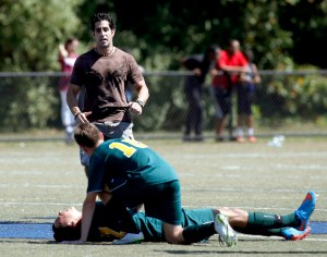 Waterbury, CT- 05 September 2015-090515CM01- Holy Cross soccer player Kevin Alves suffered a broken left wrist during the city soccer jamboree at Municipal Stadium on Sept. 5. Without a trainer present, Dr. Philip Mongelluzzo came out of the stands to help treat Alves until emergency medical personnel arrived. Monday the city approved a plan to add athletics trainers at Crosby, Kennedy, and Wilby High Schools. . Christopher Massa Republican-American