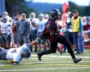 Torrington's Newton Frias attempts to find the end zone as Naugatuck's Brandon Papp  tries make a tackle during their NVL matchup in Torrington on Friday.      Christopher Massa Republican-American