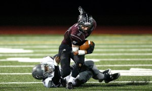 Torrington's Tyler Marens tries to gain yardage as Naugatuck's Camari Brown tries to take him down during their NVL matchup in Torrington on Friday.      Christopher Massa Republican-American