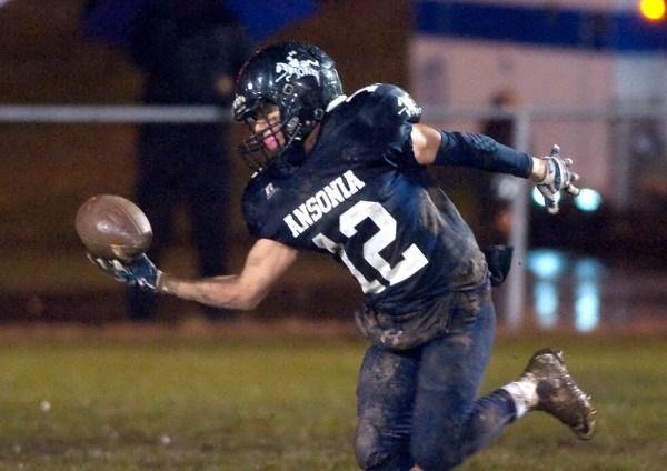 Ansonia's Justin Lopez (12) makes a one-handed interception after the ball was tipped, during their Class S Quarterfinal game against Capital Prep Tuesday at Jarvis Stadium in Ansonia.  Jim Shannon Republican-American