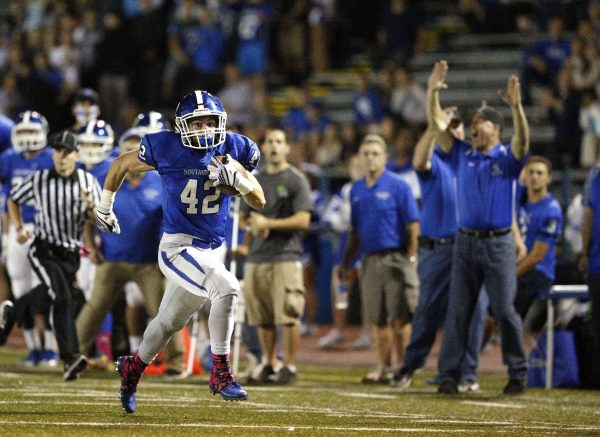 Southington's Brandon Kohl runs along the sidelines to score a touchdown against Conrad during their football matchup in Southington. (Christopher Massa/RA)
