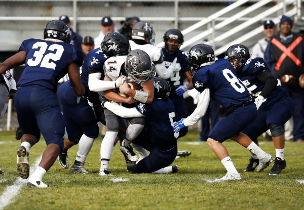 Naugatuck's Tyler Deitlebaum is wrapped up by Ansonia's Kolby Ortiz (74) and Tavieus Winder (5) during their Thanksgiving football matchup on Thursday. Also in the play are Ansonia's Malcolm Martin (32) and Justin Lopez (8). The Chargers would blank the Greyhounds, 44-0. Christopher Massa Republican-American