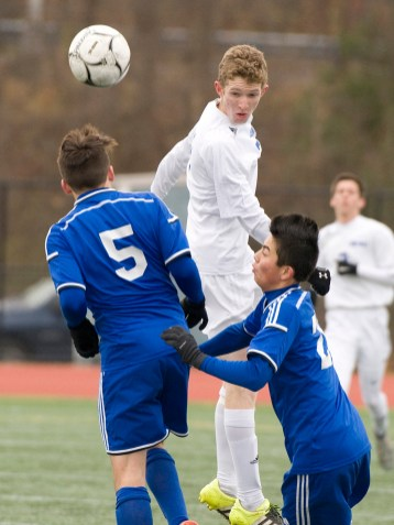 Lewis Mills' Braden Fox (2) teams the ball up field in front of Suffield's Kenneth Bigos (5) and Aidan Werenski (20) during their Class M state final game Saturday at Willow Brook Park in New Britain. Jim Shannon Republican-American