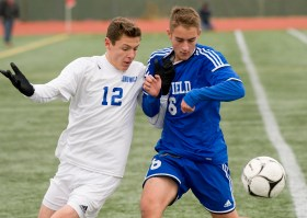 Lewis Mills' Matt Gilbert (12) Suffield's David Swan (6) run down a loose ball during their Class M state final game Saturday at Willow Brook Park in New Britain. Jim Shannon Republican-American
