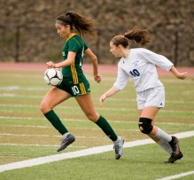 Holy Cross' Adalisse Padilla (10) runs the ball past Old Lyme's Britney DeRoehn (10) during their Class S state final game Saturday at Middletown High School. Jim Shannon Republican-American