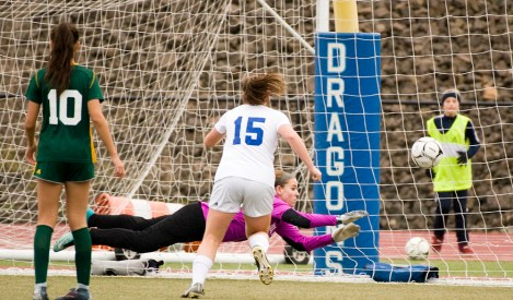 Holy Cross' Tori Schaffner makes a diving attempt but can't stop the game-winning goal by Old Lyme's Mya Johnson (12) while teammate Adalisse Padilla (10) and Old Lyme's Madeline Zrenda (15) look on during their Class S state final game Saturday at Middletown High School. Jim Shannon Republican-American