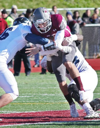 Naugatuck quarterback Michael Plasky (8) is sacked by AnsoniaÕs Garrett Cafaro (86) and Kolby Ortiz (74) Thanksgiving morning at Naugatuck High School. Ansonia won the game, 46-28. Elio Gugliotti Republican-American