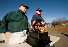 """Volunteers Stan Masayda and Don Stepanek greet fans as they stand near """"The Helmet"""" prior to Watertown's Thanksgiving Day game against Torrington Thursday at Watertown High School. Jim Shannon Republican-American"""