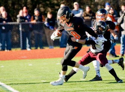 WATERTOWN, CT-112317JS12- Watertown's Thomas Hassan (8) fights off a tackle attempt by Torrington's Starling Santos (40) to score a touchdown during their Thanksgiving Day game Thursday at Watertown High School. Jim Shannon Republican-American