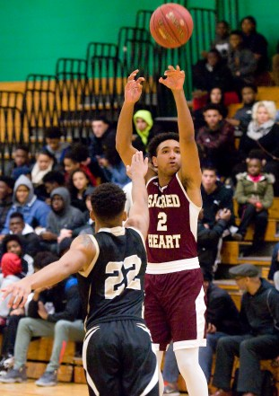 Sacred Heart's Isiah Gaiter (2) puts up a three-point shot over WCA's Marquan Watson (22) during the city boys basketball jamboree Saturday at Wilby High School in Waterbury. Jim Shannon Republican-American