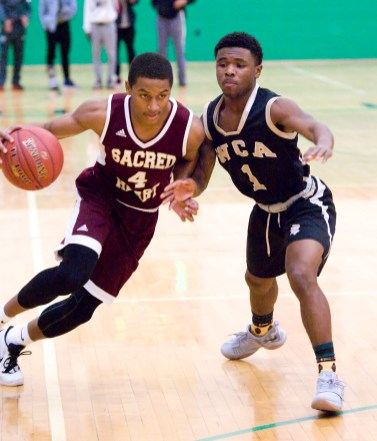 Sacred Heart's Andre Anderson (4) drives past WCA's Jadan Battle (1) during the city boys basketball jamboree Saturday at Wilby High School in Waterbury. Jim Shannon Republican-American