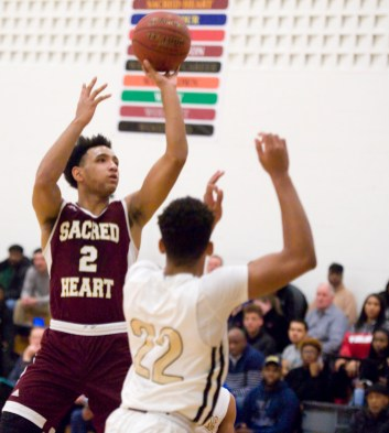 Sacred Heart's Isiah Gaiter (2) puts up a shot over WCA's Marquan Watson (22) during their game Thursday at Waterbury Career Academy. Jim Shannon Republican-American