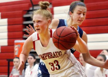 #33 Maggie Lee of Pomperaug High drives past #21 Elizabeth Breslin of Wilton during basketball action in Southbury Saturday. Steven Valenti Republican-American