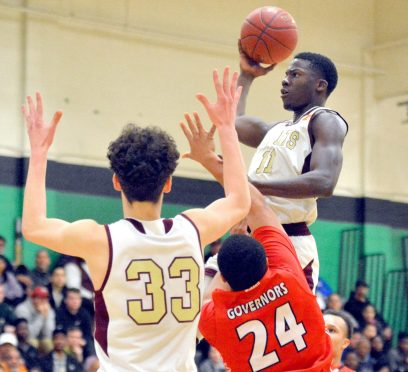 Sacred Heart's Raheem Solomon (11) puts up a shot over Wilbur Cross' William Antrum (24) as teammate Zach Francisco (33) looks on during their Division I quarterfinal game Monday at Wilby High School in Waterbury. Jim Shannon Republican-American