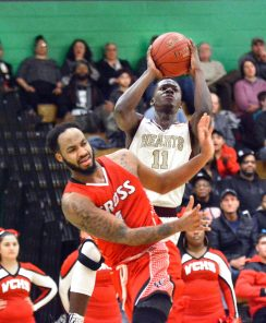 Sacred Heart's Raheem Solomon (11) puts up a shot over Wilbur Cross' Jaykeen Foreman (4) during their Division I quarterfinal game Monday at Wilby High School in Waterbury. Jim Shannon Republican-American