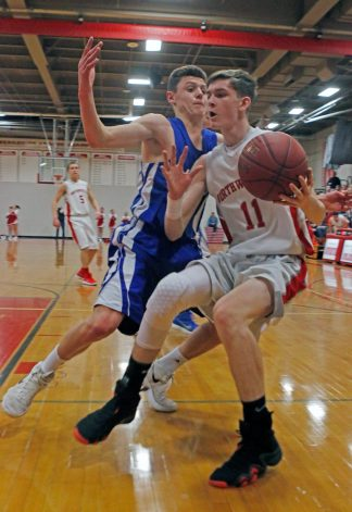 Northwestern Regional's Benjamin North ( 11 ) drives to the hoop as Lewis Mills' Matt Gilbert ( 1 ) defends during the Division IV state tournament quarterfinals Monday night at Northwestern Regional High School. Northwestern defeated Lewis Mills 58 -35 Michael Kabelka / Republican-American