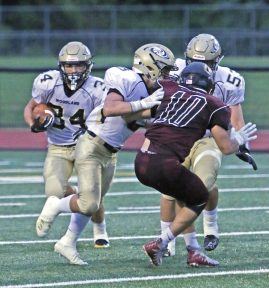Woodland's Edit Krivca (34) follows a block by Zack Cochran (5) against Torrington's Tyler Finkler during NVL action at Torrington High School Friday night. Woodland defeated Torrington Michael Kabelka / Republican-American