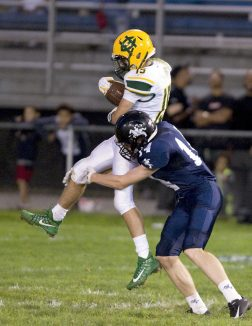 Holy Cross' Vin Graziano (15) gets brought down by Ansonia's Noah Wagnblas (14) after making a reception during their game Friday at Nolan Field in Ansonia. Jim Shannon Republican American