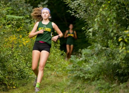 Holy Cross' Alyssa Sarracco, left, emerges from the woods during their meet with Torrington, Kennedy and Wilby Wednesday at Holy Cross High School in Waterbury. Jim Shannon Republican American