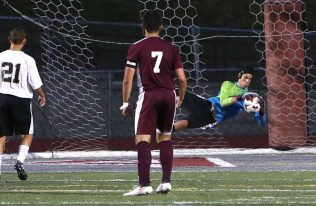 Woodland High School's goalie makes a save in front of Naugatuck High School's Tommy Martins during the boys varsity soccer game in Naugatuck on Thursday. Emily J. Reynolds. Republican-American