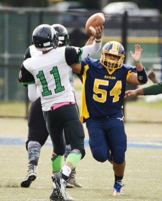 Wilby's Kenneth Figueroa (11) gets the pass off while getting pressured by Kennedy's Mike Graham (54) during their game Saturday at Municipal Stadium in Waterbury. Jim Shannon Republican American