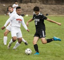 Kaynor Tech's Erick Silva (12) fires a shot past Goodwin Tech's Ayad Algahmi (7) to score a goal in the first half of their game Monday at Kaynor Tech High School in Waterbury. Jim Shannon Republican American