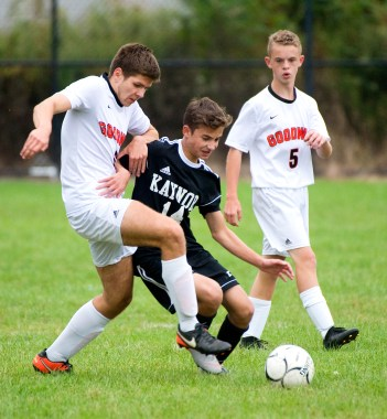Kaynor Tech's Simon Carvalho (14) gets pulled down by Goodwin Tech's Daniel Wodz (6) as Goodwin's Robert LaBlond (5) looks on, during their game Monday at Kaynor Tech High School in Waterbury. Jim Shannon Republican American