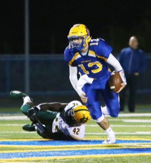 Seymour High School quarterback Ian Sadick breaks a tackle by Holy Cross High School's Alessandro Ward during the varsity football game in Seymour on Friday. Emily J. Reynolds. Republican-American