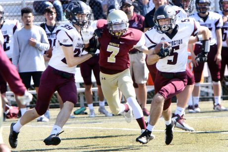 #5 Jacob Coleman of Torrington runs through the line at #7 Tom Romero of Sacred Heart/Kaynor defends during the 1st quarter of NVL football action at Municipal Stadium in Waterbury Saturday. Steven Valenti Republican-American