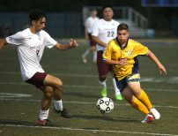 Kennedy High School's Kevin Demiraj dribbles the ball up the field past Sacred Heart High School's Gabriel Melo during the boys varsity soccer game in Waterbury on Tuesday. Emily J. Reynolds. Republican-American