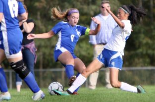 #4 Carmen Lo of Nonnewaug kicks a ball past #6 Samantha Brodeur of Litchfield during soccer action in Litchfield Tuesday. Steven Valenti Republican-American