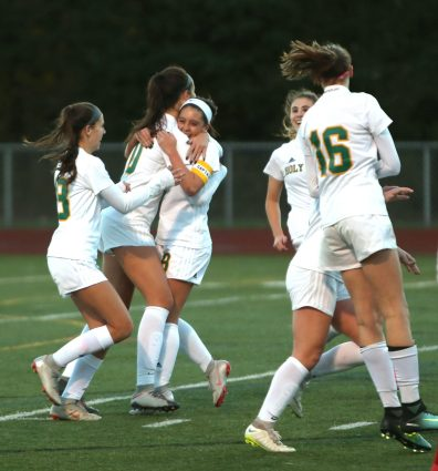 Teammates congratulate Holy Cross High School's Adalisse Padilla after she scores the game's first goal during the NVL Girls' Soccer Tournament semi-final girls varsity soccer game against Wolcott High School in Watertown on Tuesday. Emily J. Reynolds. Republican-American