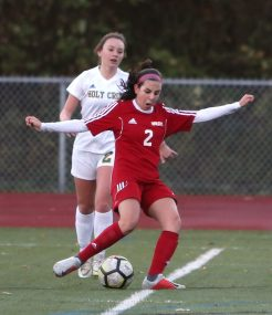 Wolcott High School's Samantha Riviezzo passes the ball up the field in front of Holy Cross High School's McKenna Ellsworth during the NVL Girls' Soccer Tournament semi-final girls varsity soccer game in Watertown on Tuesday. Emily J. Reynolds. Republican-American