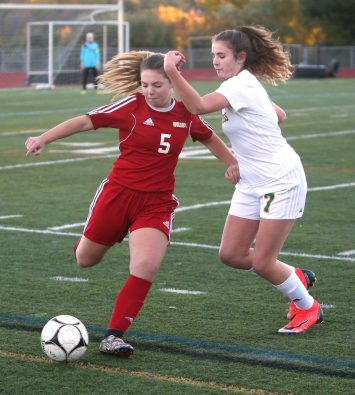 Wolcott High School's Samantha Lagasse dribbles the ball past Holy Cross High School's Sophia Vescera during the NVL Girls' Soccer Tournament semi-final girls varsity soccer game in Watertown on Tuesday. Emily J. Reynolds. Republican-American