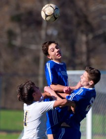 Nonnewaug's Aiden Colby (14) heads the ball while teammate William Coleman (8) and Haddam-Killingsworth's Timothy Carter (1) fight for position during their Class M tournament game Wednesday at Nonnewaug High School in Woodbury. Jim Shannon Republican American