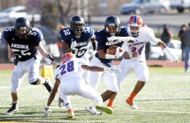 Ansonia's Tajik Bagley (4) carries the ball as Bloomfield's Thomas Norman (28) moves in for the tackle during their Class S state final matchup in New Britain on Saturday. Ansonia would go onto lose, 31-20. Christopher Massa Republican-American