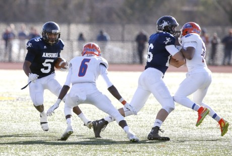 Ansonia's Tyler Bailey (5) carries the ball as Bloomfield's Ben Smith (6) moves in during their Class S state final matchup in New Britain on Saturday. Ansonia would go onto lose, 31-20. Christopher Massa Republican-American
