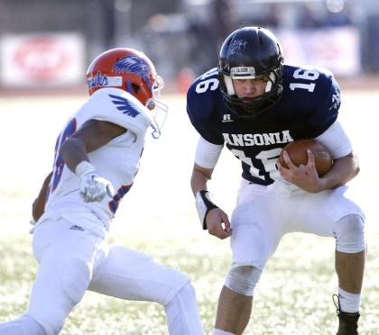 Ansonia quarterback Bryson Cafaro rushes with the ball against Bloomfield's Thomas Norman during their Class S state final matchup in New Britain on Saturday. Ansonia would go onto lose, 31-20. Christopher Massa Republican-American