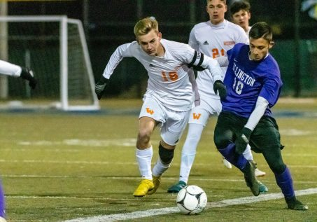 Watertown's Jake Champagne #18 and Ellington's Jackson Kupferschmid #10 battle for control of the ball along the sidelines during a Boys Soccer Class M Semifinal game between Ellington and Watertown at Municipal Stadium in Waterbury on Wednesday. Bill Shettle Republican-American