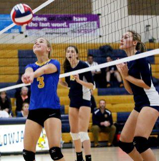 #3 Alyssa Cosciello of Seymour sets a shot as #16 Abigail Glasberg and #7 Eliza Maestri of Weston defends during the CIAC Class M volleyball championship game in East Haven Saturday. Steven Valenti Republican-American
