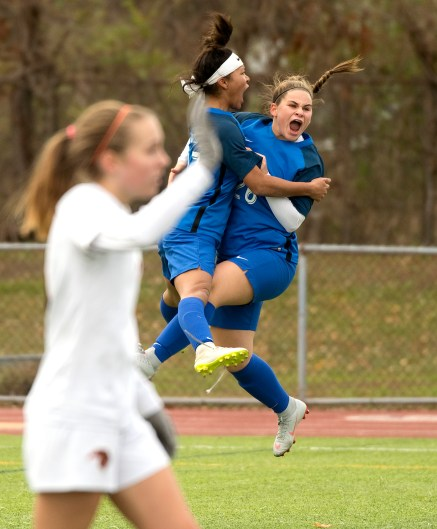 Lewis Mills' Jazzy Sztyler-Magee (27) celebrates her game tying goal with teammate Makayla Issakhani (26) during their Class M soccer championship game against Plainfield Sunday at West Haven High School. Jim Shannon Republican American