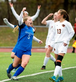 Lewis Mills' Grace Buchanan (5) celebrates her overtime goal as Plainfield's Karley Belsilie (13) looks on during their Class M soccer championship game Sunday at West Haven High School. Jim Shannon Republican American