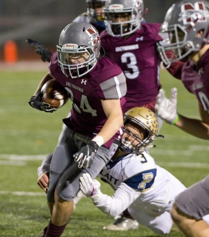 Naugatuck's Jeff Schebell (24) is brought down by Platt's Lorenzo Sanson (3) but not before running for a first down during their Class L quarterfinal game Tuesday at Naugatuck High School. Jim Shannon Republican American